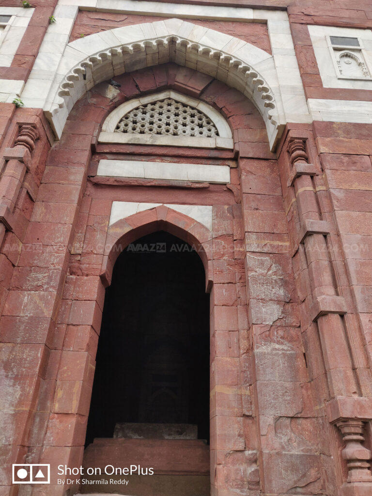 The doorway with marble jali screens and white marble cuspings
