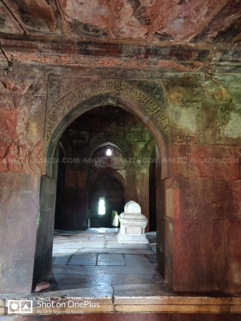 Red sandstone arches with Quranic Inscriptions