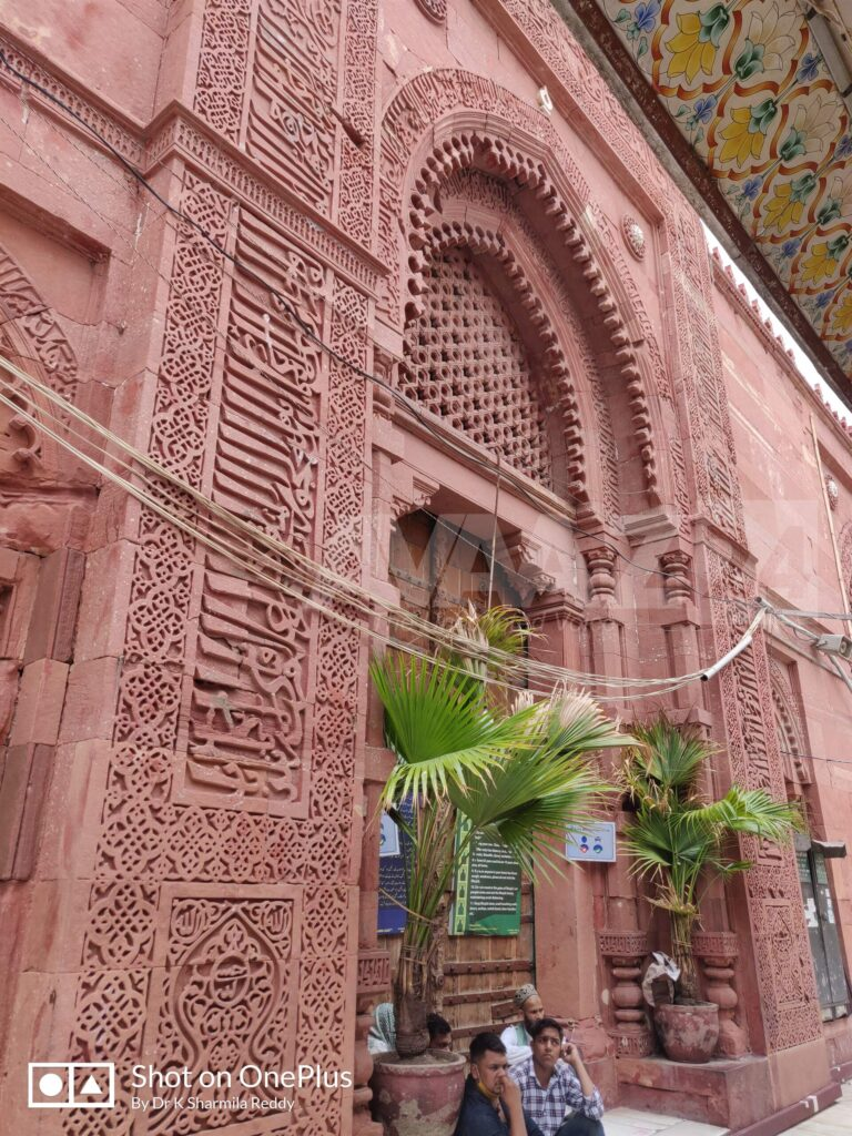 Beautifully carved Quranic Ayats on the red sandstone walls of Jamat Khana Mosque